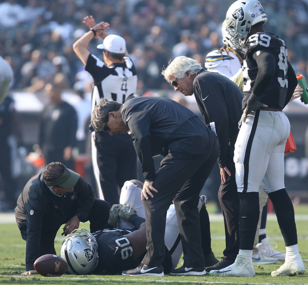 Oakland Raiders defensive tackle Johnathan Hankins (90) lays injured on the field as trainers look at him during the first half of their NFL game against the Los Angeles Chargers in Oakland, Calif ...