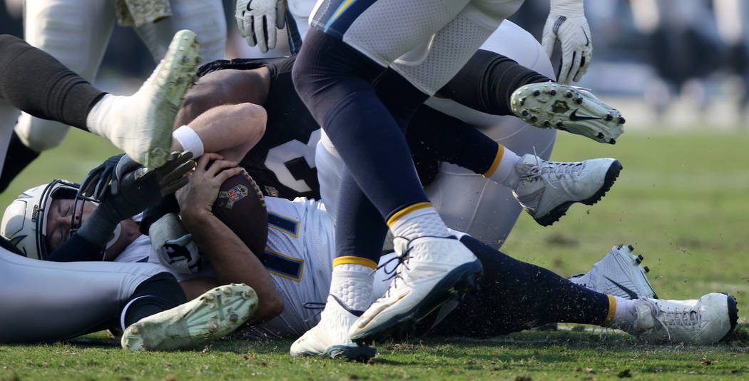Los Angeles Chargers quarterback Philip Rivers (17) is sacked by Oakland Raiders defensive tackle Maurice Hurst (73) during the first half of their NFL game in Oakland, Calif., Sunday, Nov. 11, 20 ...