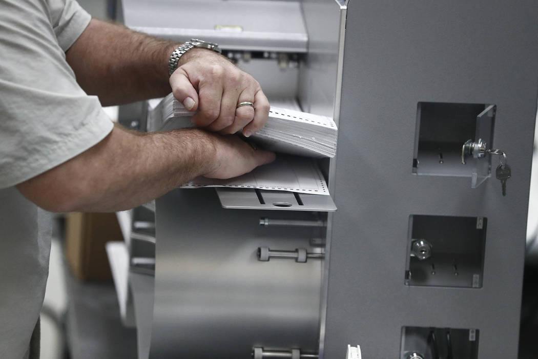 A worker loads ballots into machines at the Broward County Supervisor of Elections office during a recount on Sunday, Nov. 11, 2018, in Lauderhill, Fla. (AP Photo/Brynn Anderson)
