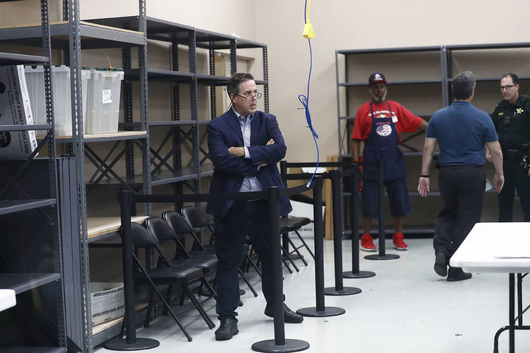 A party observer watches as workers load ballots into machines at the Broward County Supervisor of Elections office during a recount on Sunday, Nov. 11, 2018, in Lauderhill, Fla. (AP Photo/Brynn A ...