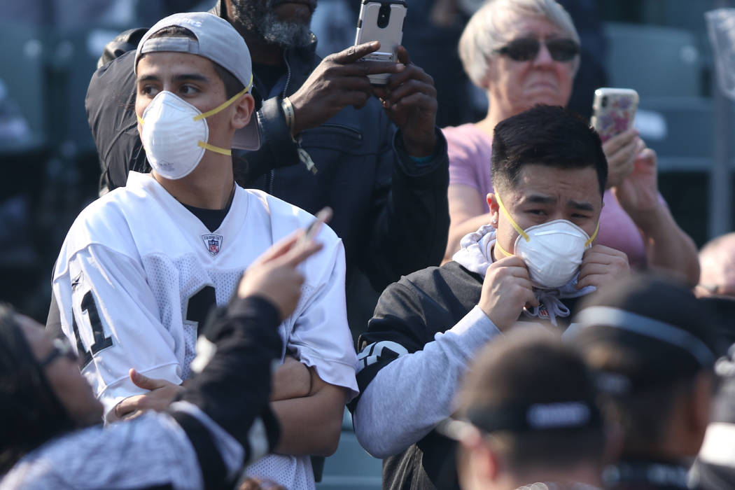 Fans during the Oakland Raiders vs. Los Angeles Chargers NFL game wear protective masks due to smoke from the Camp Fire burning north of the Oakland-Alameda County Coliseum in Oakland, Calif., Sun ...