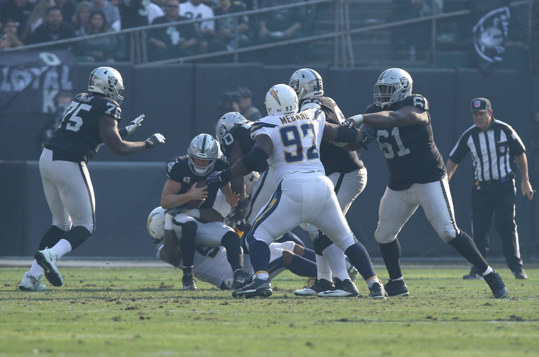 Oakland Raiders quarterback Derek Carr (4) is sacked by Los Angeles Chargers defensive tackle Darius Philon (93) and defensive end Isaac Rochell (98) during the first half of their NFL game in Oak ...