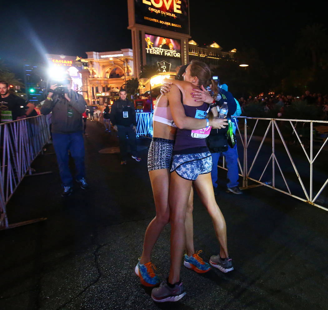 First place women's finisher Hannah McInturff, left, hugs second place women's finisher Jessica Sams after she crosses the finish line during the 2018 Rock 'n' Roll Marathon on the Strip in Las Ve ...