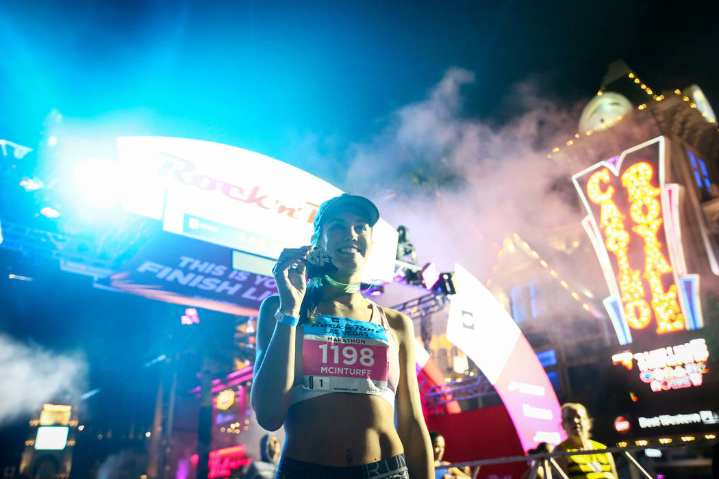 First place women's finisher Hannah McInturff poses with her medal in front of the finish line during the 2018 Rock 'n' Roll Marathon on the Strip in Las Vegas, Sunday,Nov. 11, 2018. Caroline Breh ...