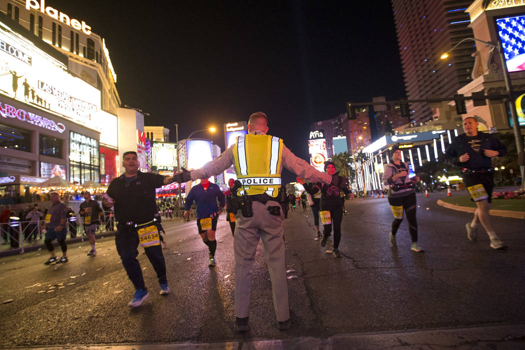 Metro officer Brice Clements high fives passing runners during the 2018 Rock 'n' Roll Marathon on the Strip in Las Vegas on Sunday, Nov. 11, 2018. Richard Brian Las Vegas Review-Journal @vegasphot ...