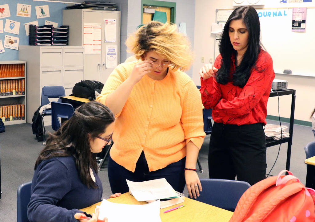 Hana Helfand, left sitting, copy editor of the Grizzly Growler, student newspaper, edits Laura Solsona's, left, story as Tara Verderosa, a journalism teacher at Spring Valley High School, looks on ...