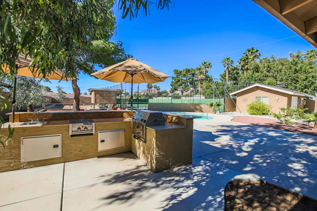 The outdoor kitchen is near the pool and tennis court. (Xpand Realty)