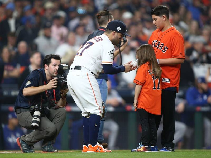Oct 28, 2017; Houston, TX, USA; Hailey Dawson (right) greets Houston Astros second baseman Jose Altuve (27) after throwing out the ceremonial first pitch before game four of the 2017 World Series ...