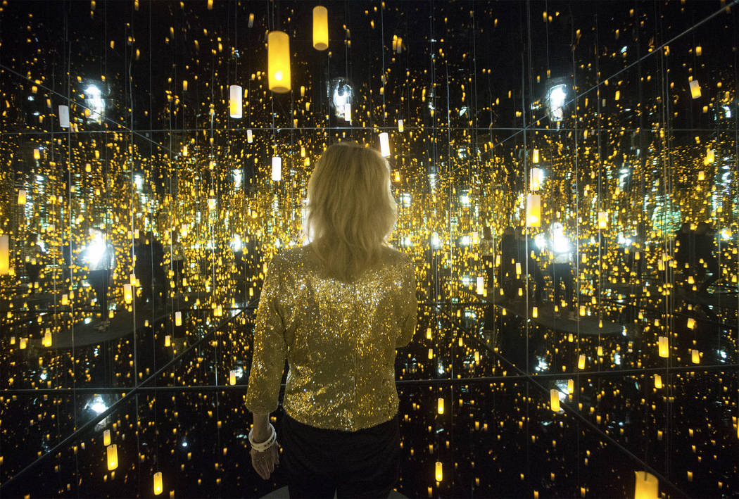 "Dawn Michelle Baude explores the ""Infinity Mirrored Room"" at Yayoi Kusama's new exhibit at Bellagio Gallery of Fine Art on Friday, Nov. 16, 2018, in Las Vegas. Benjamin Hager Las Vegas ..."