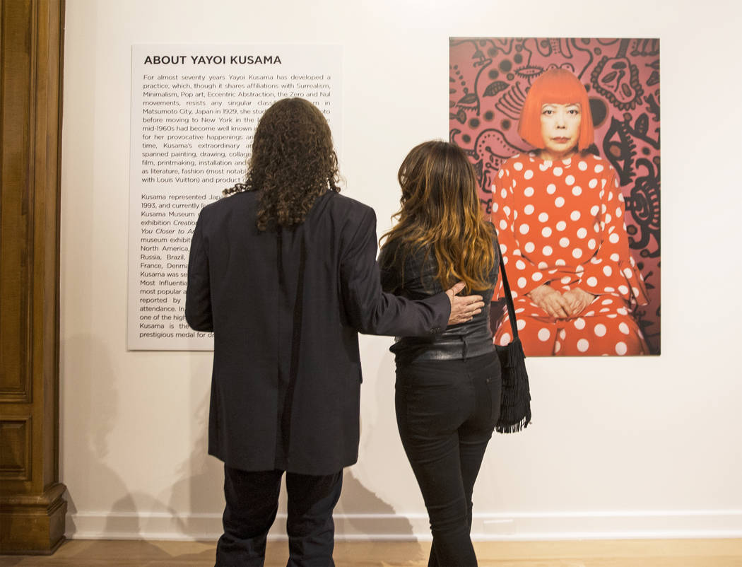 Matt Kelemen, left, and Gisela Lacayo read background information on artist Yayoi Kusama at her new exhibit at Bellagio Gallery of Fine Art on Friday, Nov. 16, 2018, in Las Vegas. Benjamin Hager ...