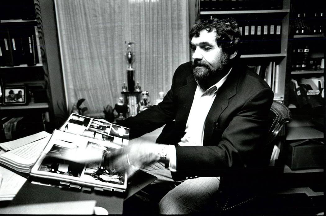 Michael Cherry looks through a photo album of MGM Fire victims at his office. (Toru Kawana/Las Vegas Review-Journal)