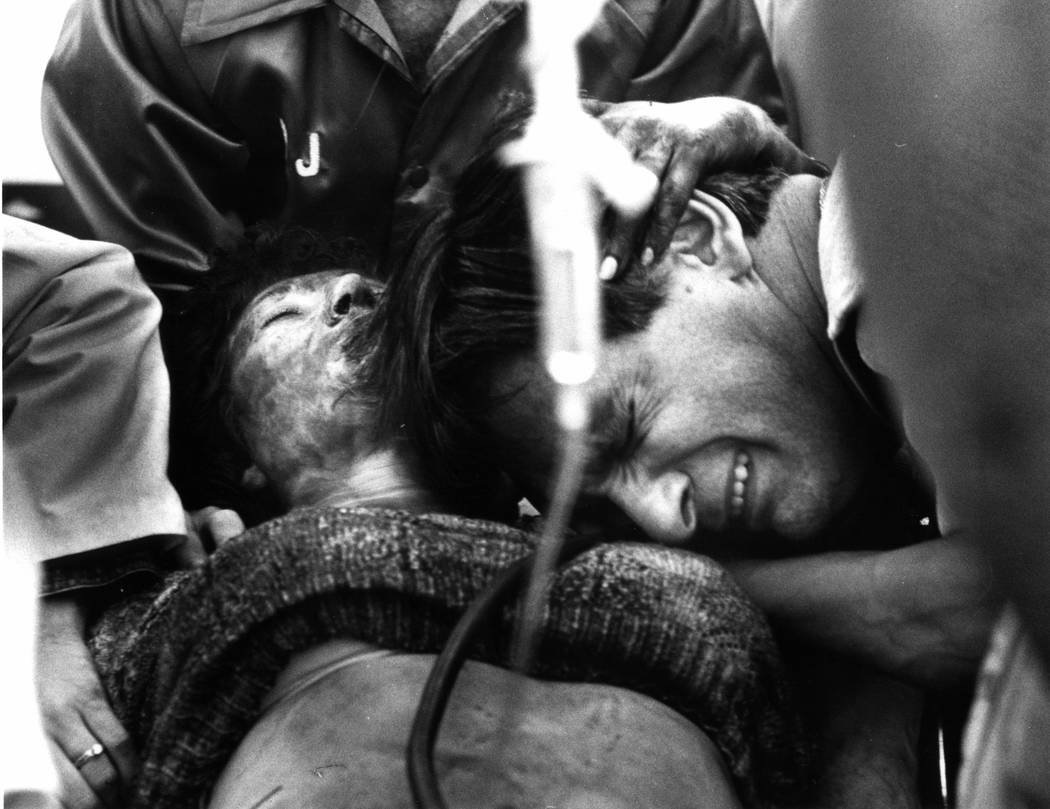 FIGHTING FOR LIFE: An unidentified husband grieves over his wife who was burned Friday, Nov. 21, 1980, in a monumental fire at the MGM Grand Hotel. The woman, who survived the fire, was taken to a ...