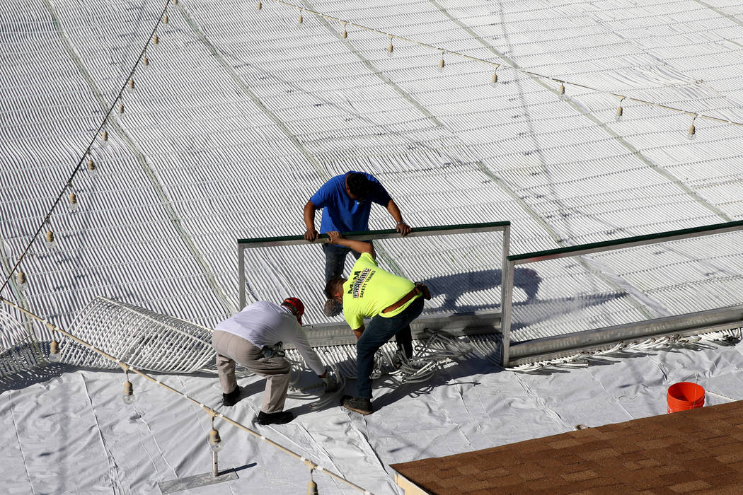 Workers flatten Glycol tubes used to create ice for the under construction Rock Rink temporary ice rink at The Lawn in Downtown Summerlin in Las Vegas Tuesday, Nov. 6, 2018. K.M. Cannon Las Vegas ...