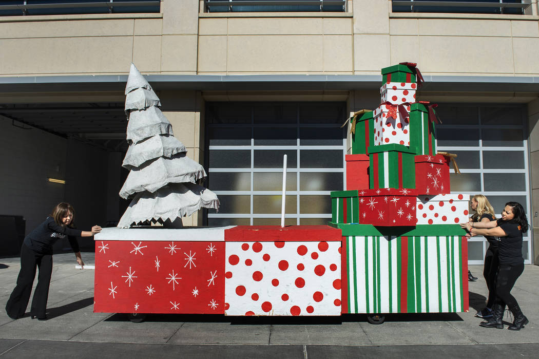 Gwynn Lloyd-Hughes, left, Angelina Savage and Lissett Sanchez wheel out the Elves Workshop float in preparation for the annual Downtown Summerlin holiday parade in Las Vegas, Wednesday, Nov. 14, 2 ...