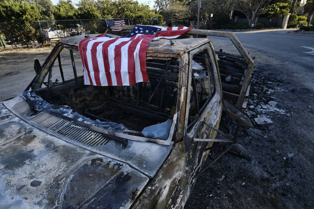 An American flag is draped over the charred remains of an old pickup truck entering Point Dume along the pacific coast highway in Malibu, Calif., on Sunday Nov. 11, 2018. (AP Photo/Richard Vogel)