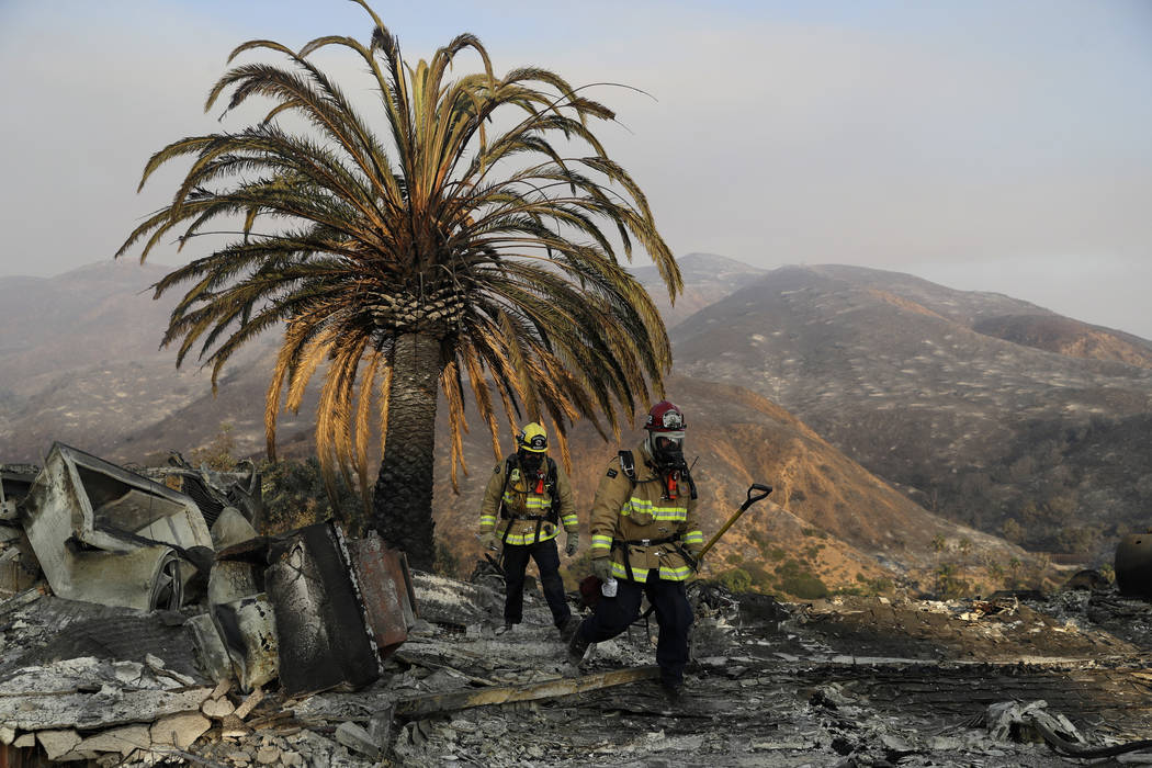 Firefighters Jason Toole, right, and Brent McGill with the Santa Barbara Fire Dept. walk among the ashes of a wildfire-ravaged home after turning off an open gas line on the property Saturday, Nov ...
