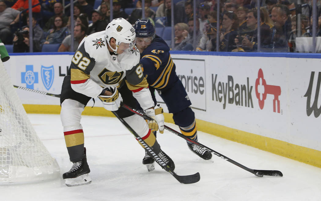 Buffalo Sabres defenseman Jake McCabe (19) and Vegas Golden Knights forward Thomas Nosek (92) battle for the puck during the first period of an NHL hockey game, Monday, Oct. 8, 2018, in Buffalo N. ...
