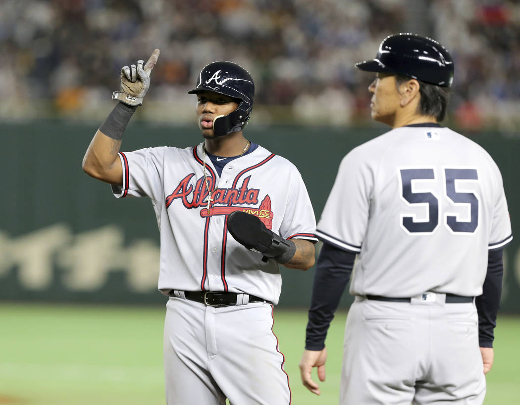 MLB All-Star Ronald Acuna Jr. of the Atlanta Braves points to the ceiling while talking with first base coach Hideki Matsui (55) after teammate Juan Soto of the Washington Nationals ground-rule fl ...