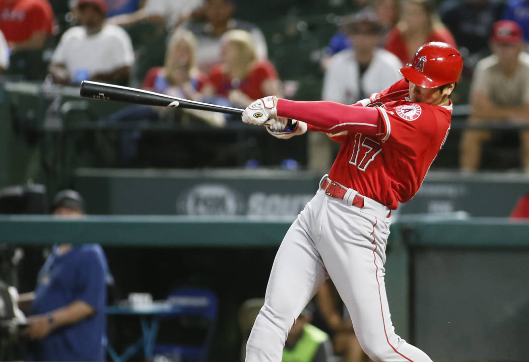 In this Sept. 5, 2018, file photo, Los Angeles Angels' Shohei Ohtani follows through on a two-run home run against the Texas Rangers during the eighth inning of a baseball game in Arlington, Texas ...