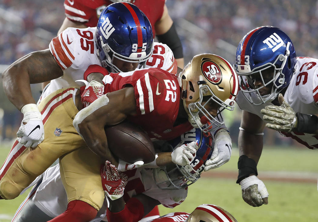 San Francisco 49ers running back Matt Breida (22) is tackled by New York Giants defensive end B.J. Hill (95), free safety Curtis Riley, center, and middle linebacker B.J. Goodson (93) during the s ...