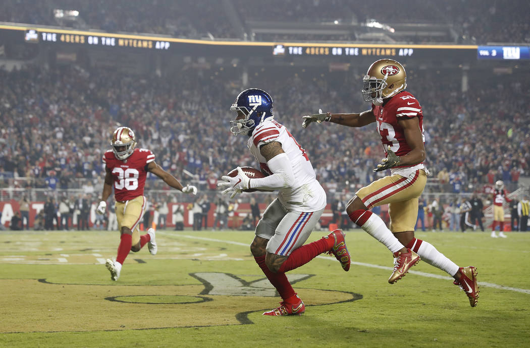 New York Giants wide receiver Odell Beckham Jr., center, scores in front of San Francisco 49ers cornerback Ahkello Witherspoon, right, and defensive back Antone Exum (38) during the second half of ...