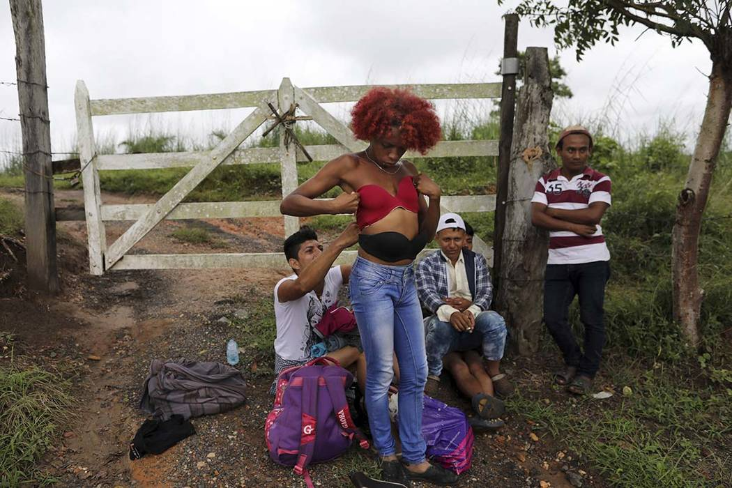 Honduran transgender Alexa Amaya, who is traveling with the migrant caravan hoping to reach the U.S. border, tries on a pushup bra she selected from a pile of donated clothing left alongside the r ...
