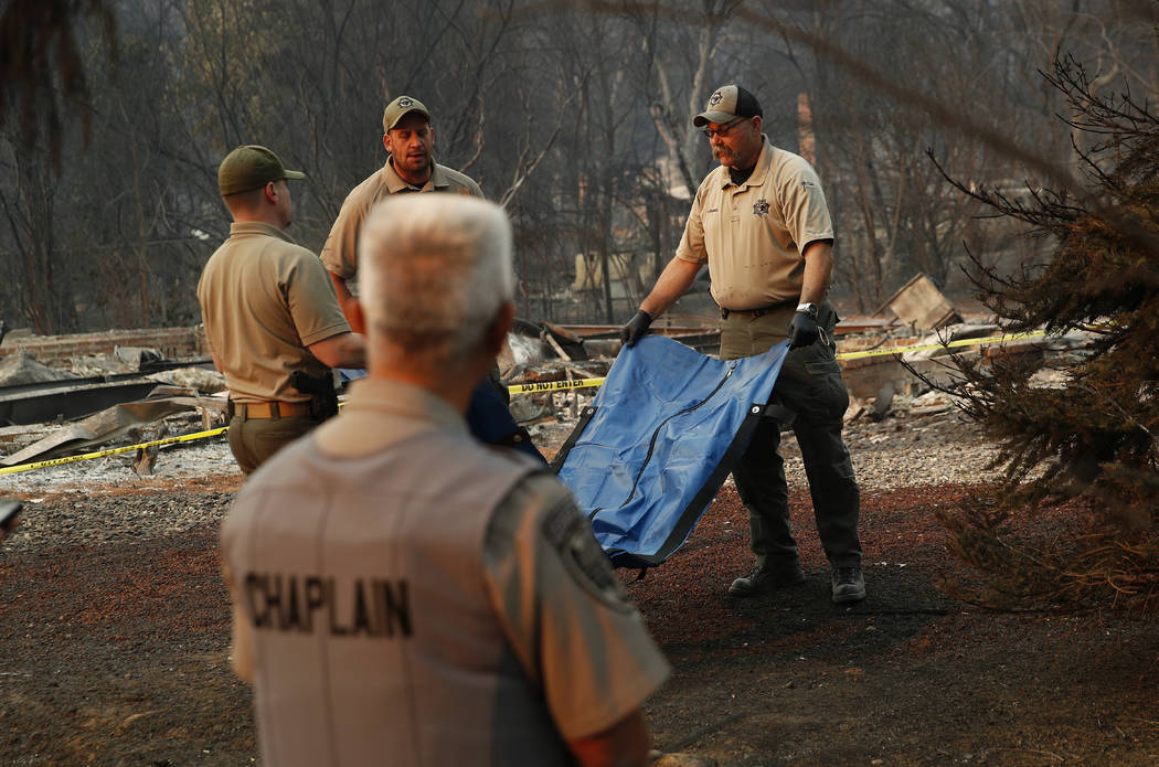 Deputy Coroner Justin Sponhaltz, right, of the Mariposa County Sheriff's Office, carries a bag with human remains found at a burned out home at the Camp Fire, Sunday, Nov. 11, 2018, in Paradise, C ...