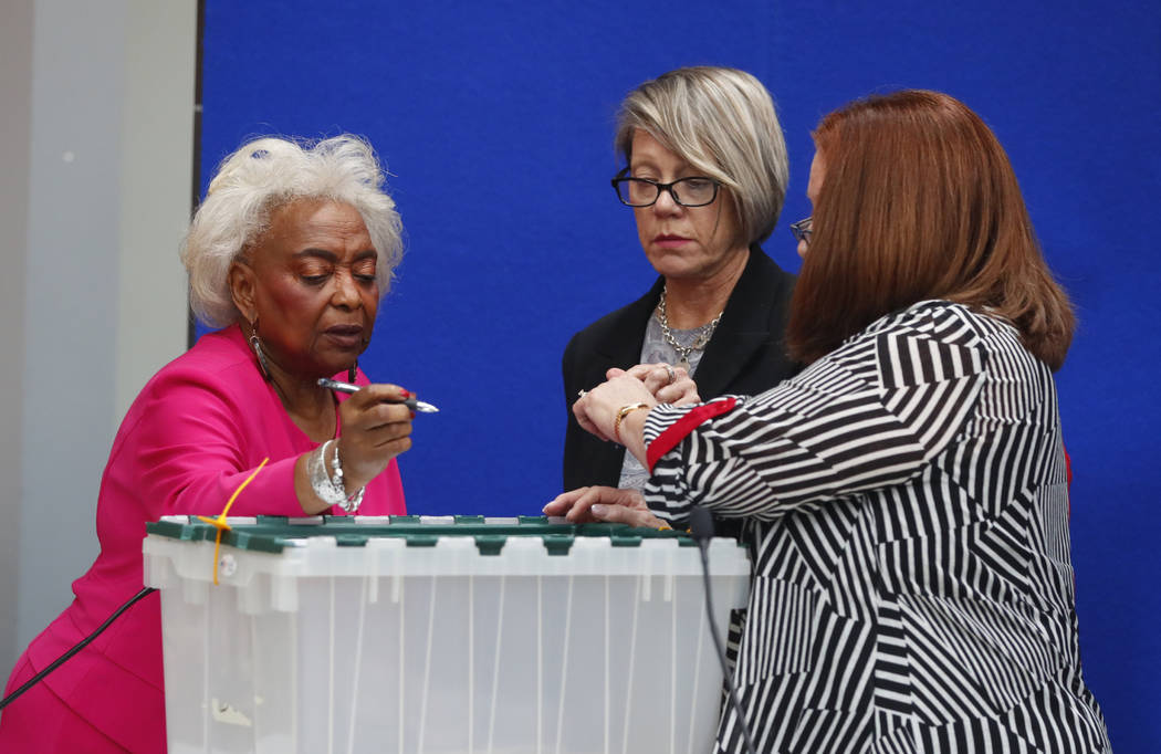 Broward County Supervisor of Elections Brenda Snipes, left, Board chair Judge Betsy Benson, center, and Board member Judge Deborah Carpenter-Toye, sign off on a sealed bin that will be sent to the ...