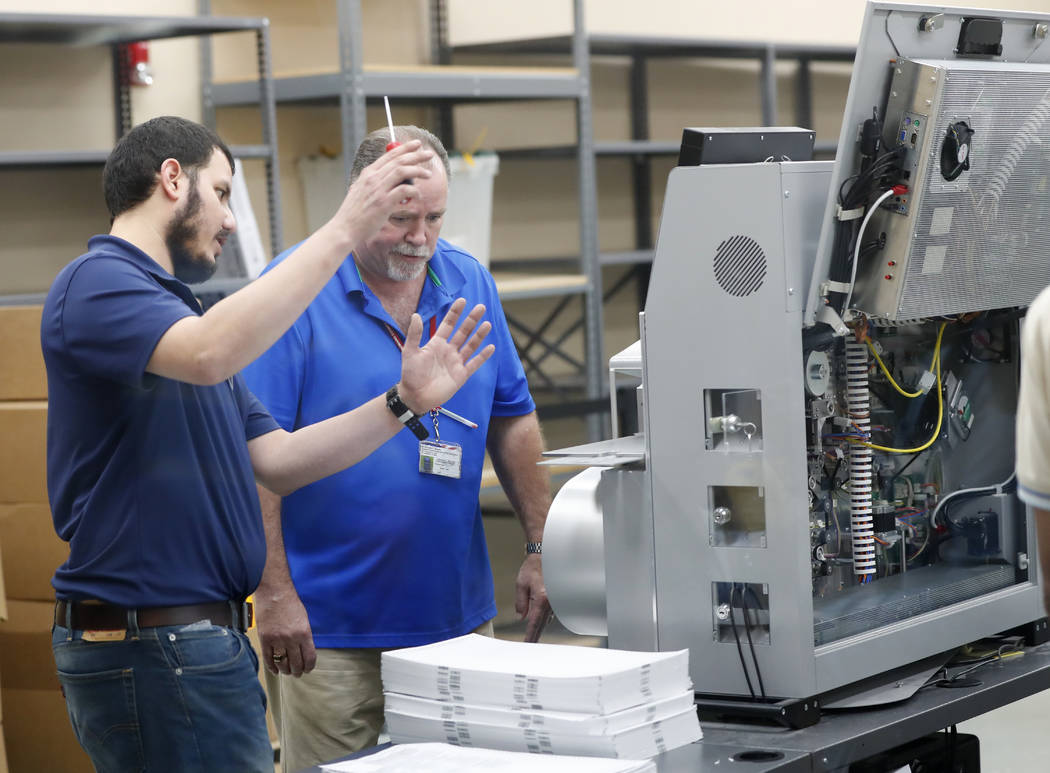 Employees at the Broward County Supervisor of Elections office check a machine as they sort ballots before being counted, Monday, Nov. 12, 2018, in Lauderhill, Fla. (AP Photo/Wilfredo Lee)