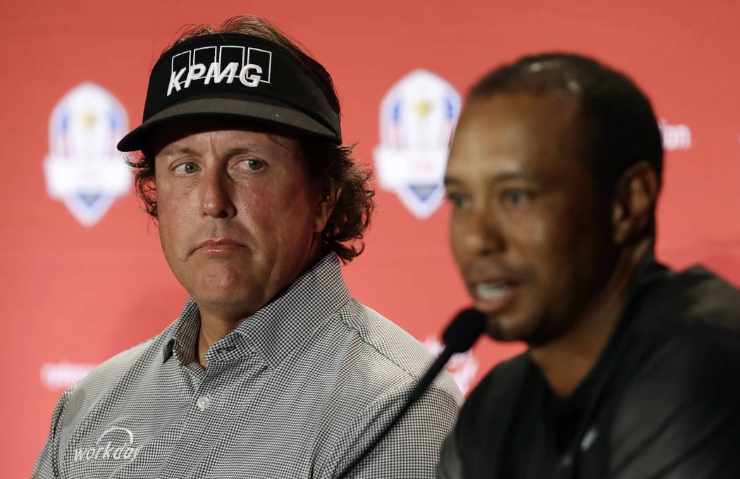 Phil Mickelson, left, listens to Tiger Woods speak during a news conference where they were announced as captain's picks for the 2018 U.S. Ryder Cup Team, Tuesday, Sept. 4, 2018, in West Conshohoc ...