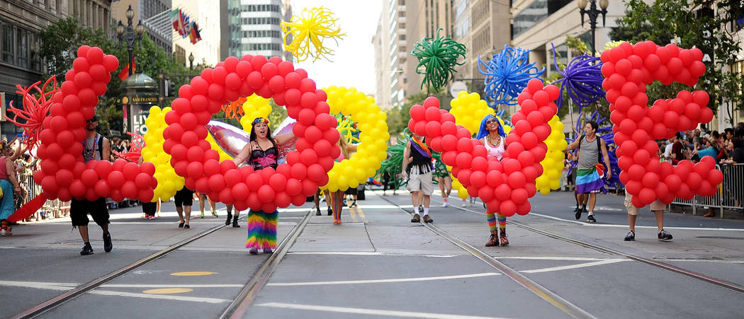 """Deanna Ryan carries the letter """"O"""" as part of a balloon brigade spelling """"love"""" during San Francisco's 43rd annual Gay Pride parade on Sunday, June 30, 2013. (AP Photo/Noah Be ..."""
