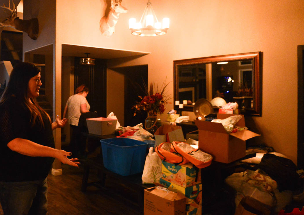 """Most of this was donated,"" Stacie Power says of the clothes, diapers and sundries that cover her kitchen table Tuesday, Nov. 13, 2018. Power took in family members displaced by the Camp ..."