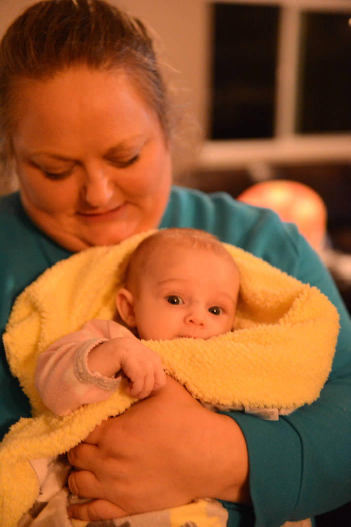 Oblivious to the fact that she's been evacuated and displaced, Adison Power, 3-months-old, smiles and enjoys the attention Tuesday, Nov. 13, 2018, in the arms of aunt Tria Boyette, at Stacie Power ...