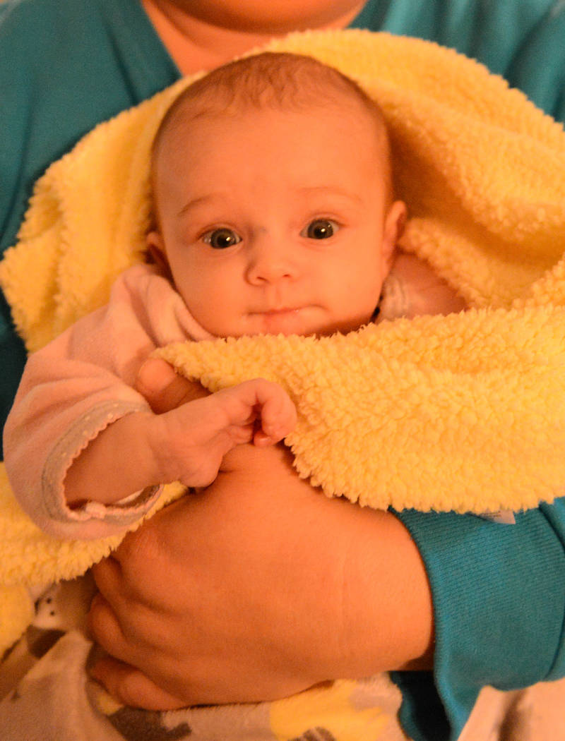 Oblivious to the fact that she's been evacuated and displaced, Adison Power, 3-months-old, smiles and enjoys the attention Tuesday, Nov. 13, 2018, at her aunt Stacie Power's home. Power took in he ...