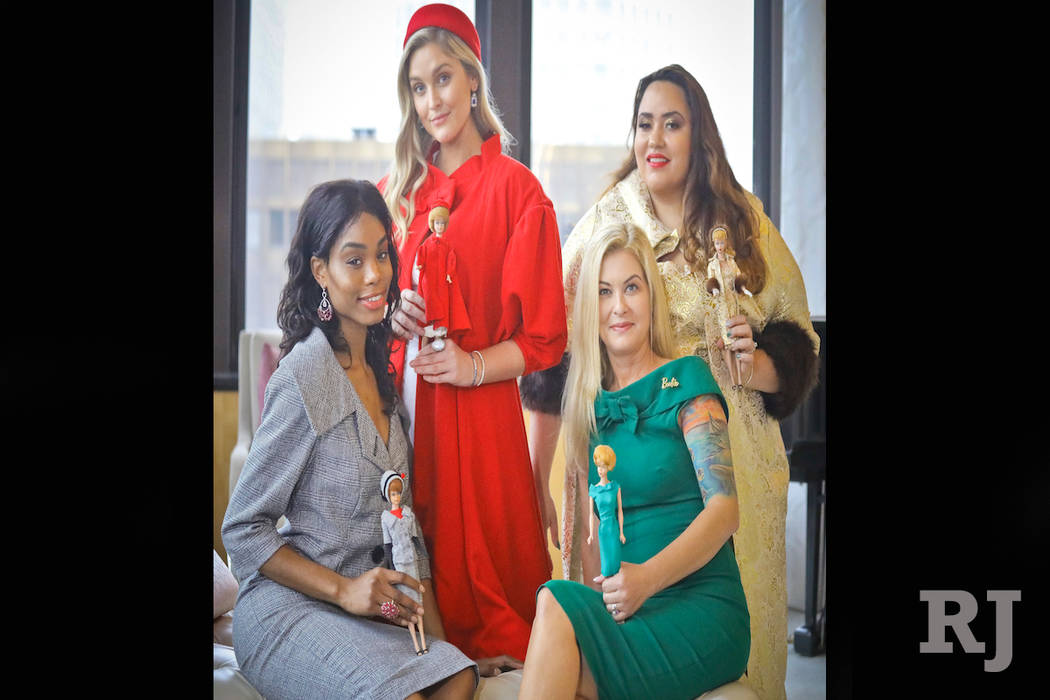 In this Nov. 5, 2018 photo, designer Katie Echeverry, seated right, join models Tiffany Hendrix, seated left, Kelsey Elliott, standing left, and Lori Moran, wearing outfits from a Barbie inspired ...