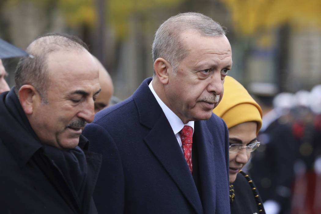 Turkish President Recep Tayyip Erdogan, right, and Turkish Foreign Minister Mevlut Cavusoglu leave the Arc de Triomphe after attending a ceremony as part of the commemorations marking the 100th an ...