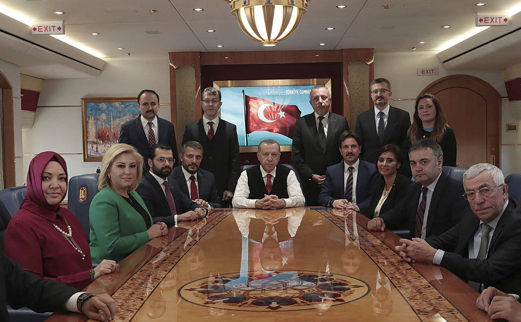 In this photo taken Monday, Nov. 12, 2018, Turkish President Recep Tayyip Erdogan poses for photos with Turkish journalists aboard his plane. Erdogan said Monday Nov. 12, 2018, his country is &qu ...