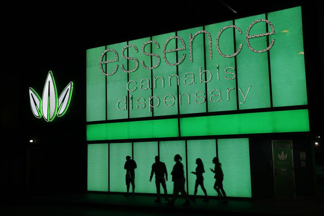 In this April 16, 2018, file photo, people stand outside after shopping at the Essence cannabis dispensary in Las Vegas. (AP Photo/John Locher)