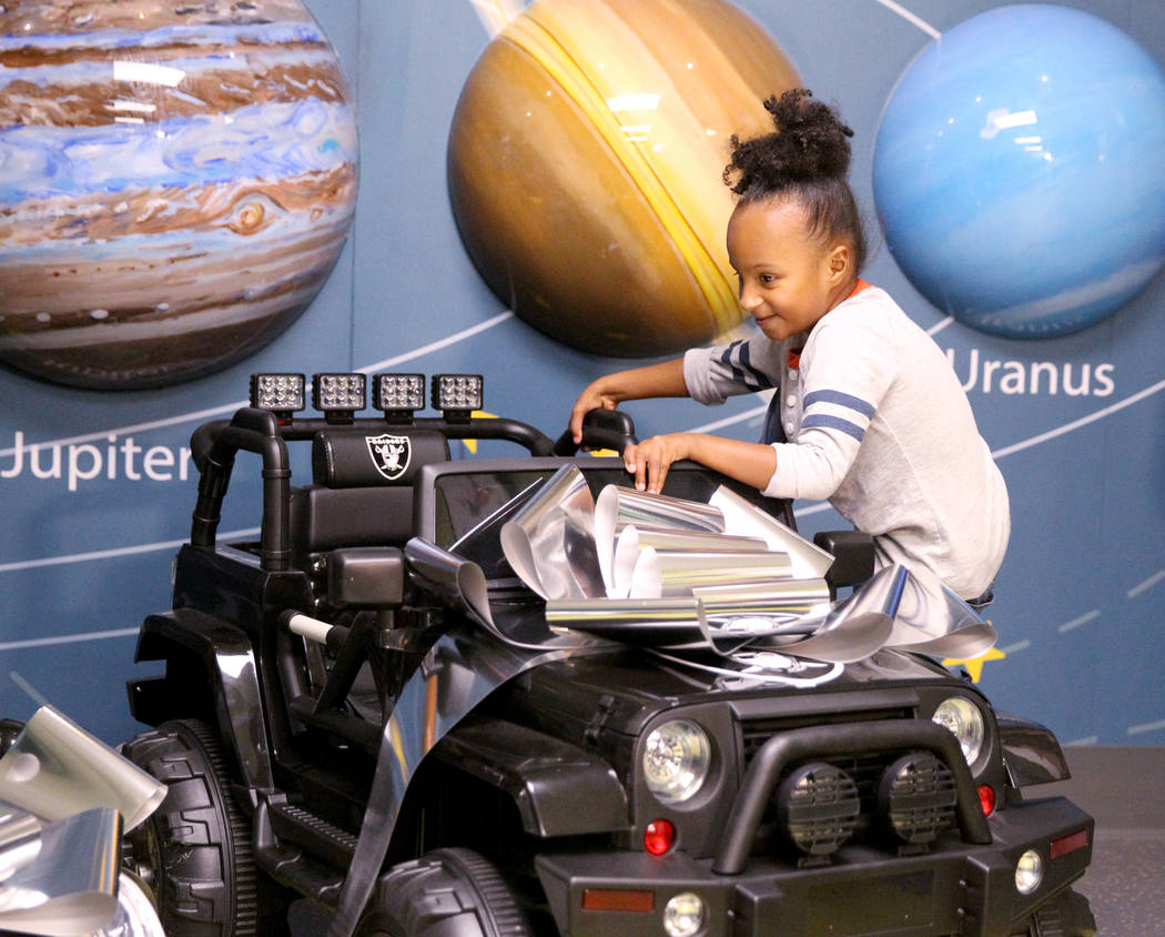 Harmony Lund, 4, climbs into a Raiders-themed toy car at University Medical Center Children's Hospital in Las Vegas Tuesday, Nov. 13, 2018, during a visit from Raiders alumni and Raiderettes. The ...