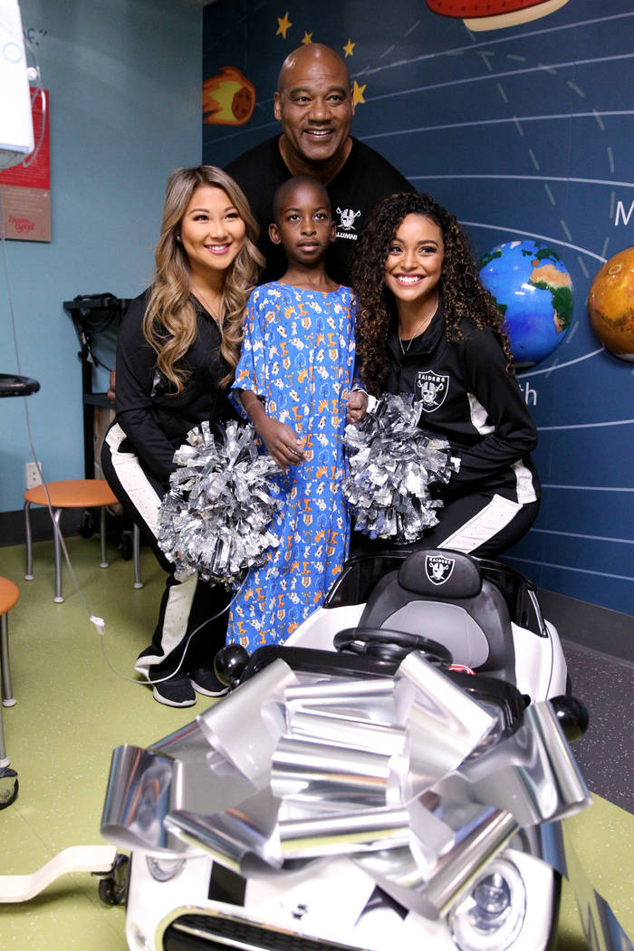 Justice Truitt, 8, poses with Raiders alumnus Chris McLemore and Raiderettes Helina, left, and Sierra at University Medical Center Children's Hospital in Las Vegas Tuesday, Nov. 13, 2018. The Raid ...