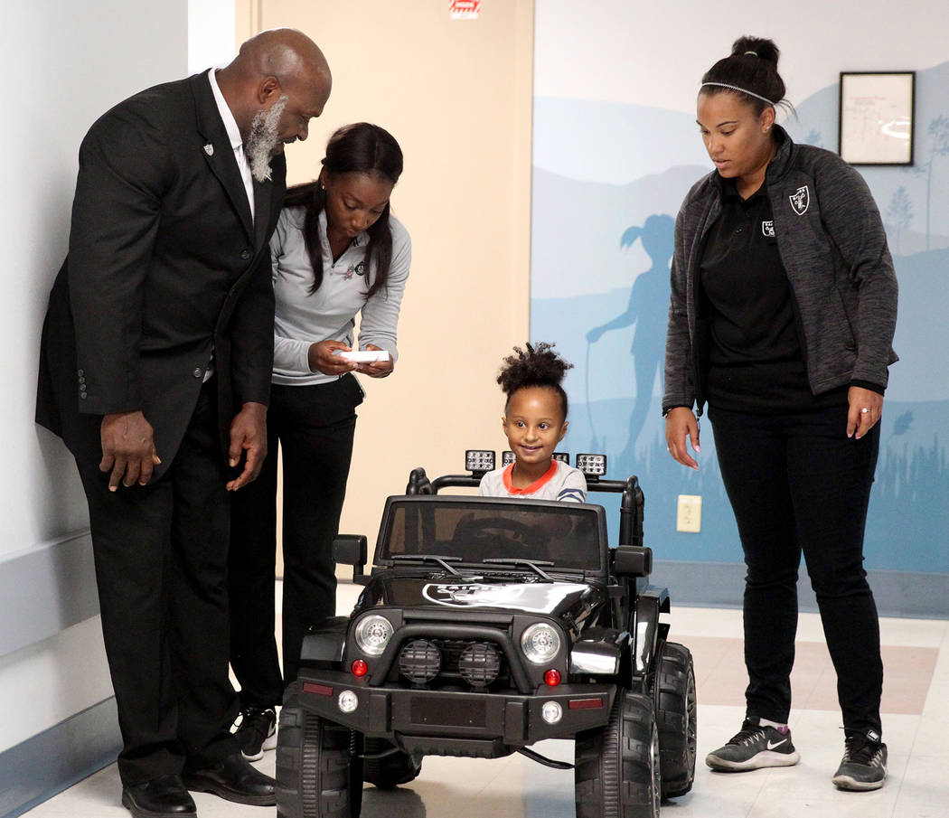 Harmony Lund, 4, drives down the hall with Raiders alumnus Roy Hart Jr. at University Medical Center Children's Hospital in Las Vegas Tuesday, Nov. 13, 2018. Looking on are Faith Williams, right, ...
