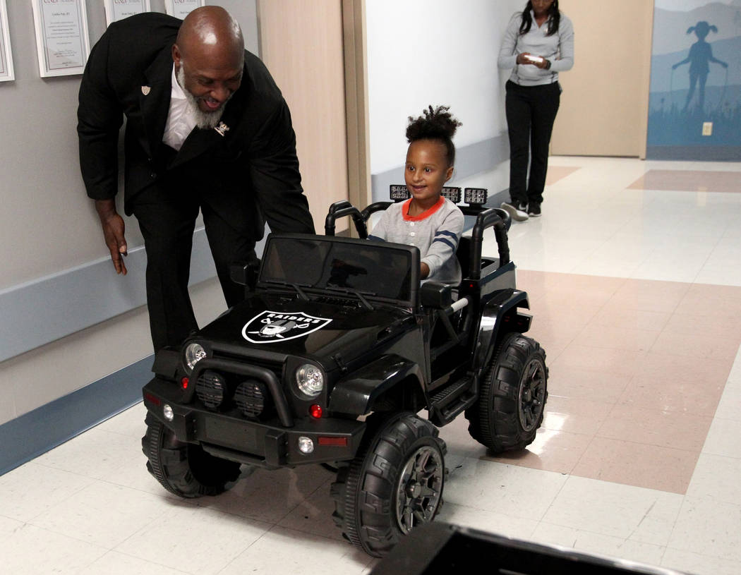 Harmony Lund, 4, drives down the hall with Raiders alumnus Roy Hart Jr. at University Medical Center Children's Hospital in Las Vegas Tuesday, Nov. 13, 2018. The Raiders contributed $5,000 in supp ...