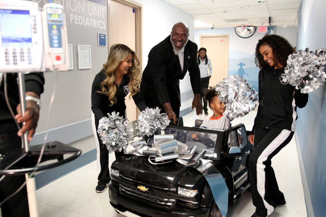 Harmony Lund, 4, with Raiders alumnus Roy Hart Jr. and Raiderettes Helina, left, and Sierra at University Medical Center Children's Hospital in Las Vegas Tuesday, Nov. 13, 2018. The Raiders contri ...