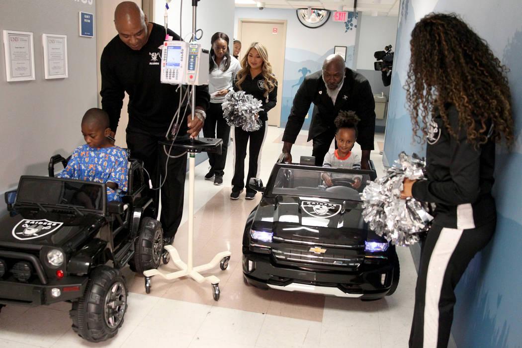Justice Truitt, 8, with Raiders alumnus Chris McLemore, left, and Harmony Lund, 4, with Raiders alumnus Roy Hart Jr., drive cars at University Medical Center Children's Hospital in Las Vegas Tuesd ...