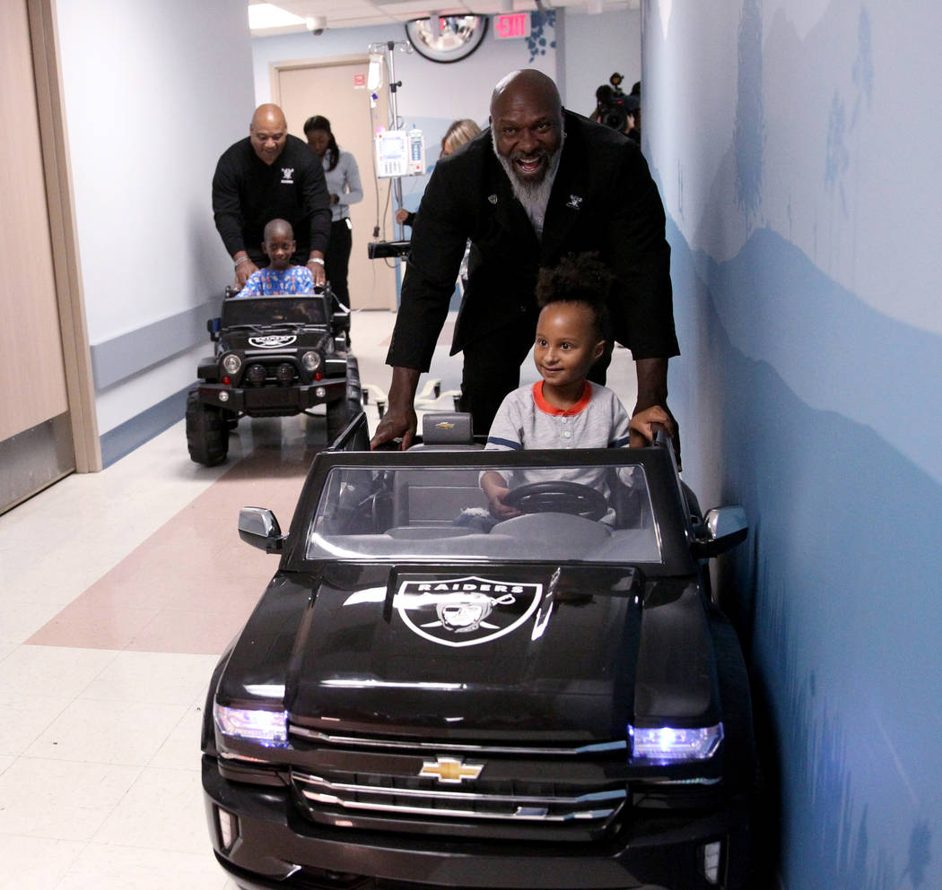 Harmony Lund, 4, with Raiders alumnus Roy Hart Jr., right, and Justice Truitt, 8, with Raiders alumnus Chris McLemore drive cars at University Medical Center Children's Hospital in Las Vegas Tuesd ...