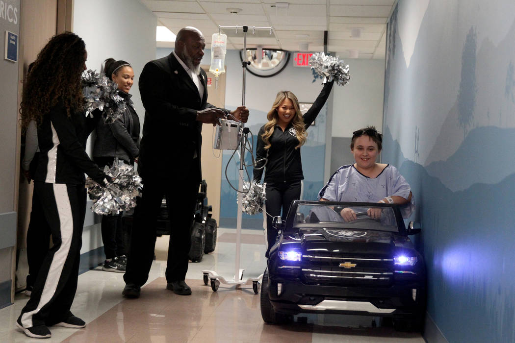 Craig Schwarz, 13, drives down the hall at University Medical Center Children's Hospital in Las Vegas Tuesday, Nov. 13, 2018. Looking on, from left, are Raiderette Sierra, Faith Williams with Raid ...
