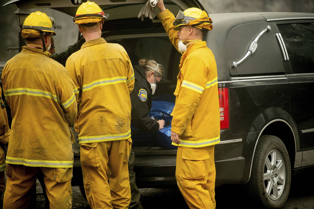 A Butte County sheriff's deputy makes a note while recovering the body of a Camp Fire victim at the Holly Hills Mobile Estates on Wednesday, Nov. 14, 2018, in Paradise, Calif. Thousands of homes w ...