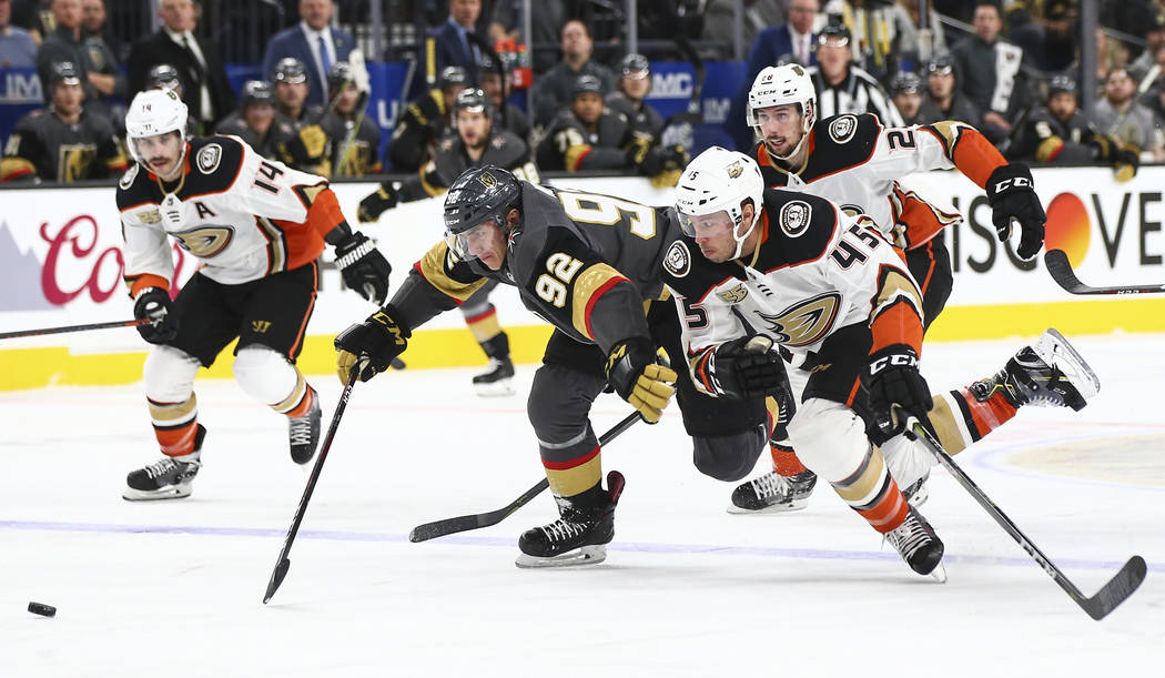 Golden Knights left wing Tomas Nosek (92) and Anaheim Ducks defenseman Andy Welinski (45) chase after the puck during the first period of an NHL hockey game at T-Mobile Arena in Las Vegas on Wedne ...