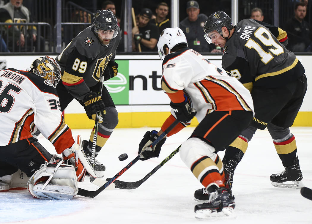 Golden Knights forwards Alex Tuch (89) and Reilly Smith (19) try to get the puck in against Anaheim Ducks goaltender John Gibson (36) and defenseman Brandon Montour (26) during the first period of ...
