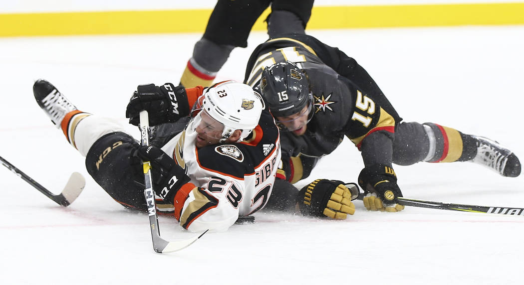 Anaheim Ducks center Brian Gibbons (23) and Golden Knights defenseman Jon Merrill (15) fall to the ice while battling for the puck during the second period of an NHL hockey game at T-Mobile Arena ...